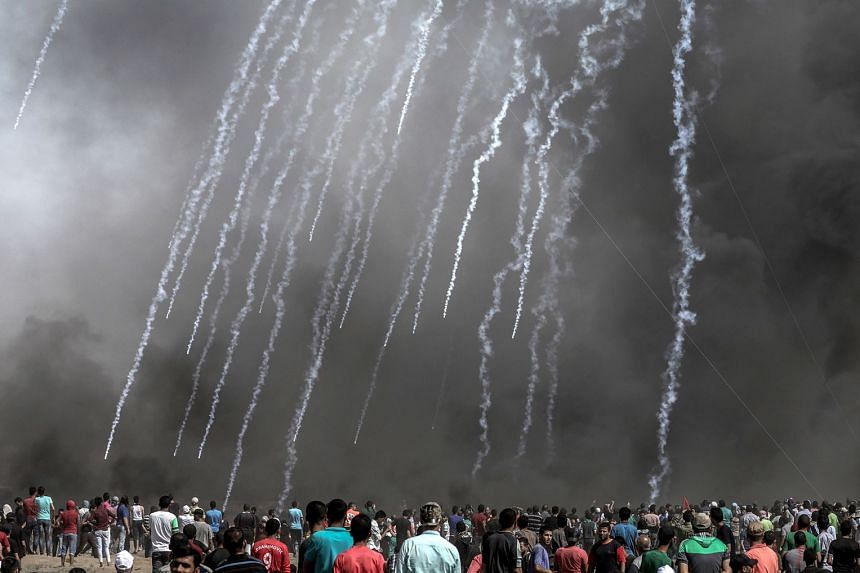 Israeli soldiers fire tear-gas at Palestinian protesters during border clashes on June 8, 2018.