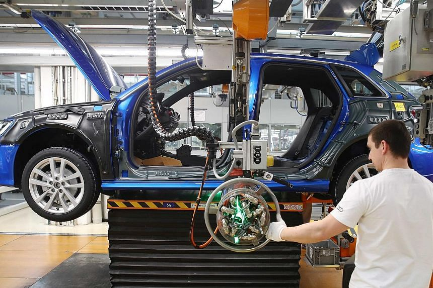 A worker assembles a new Audi at the production line of the German car manufacturer's plant in Ingolstadt, Germany.