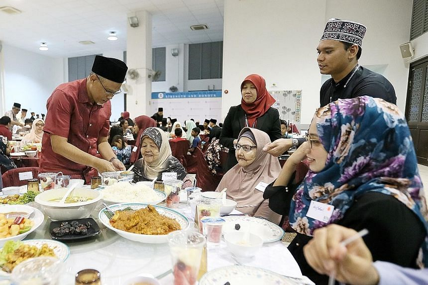 Minister-in-charge of Muslim Affairs Masagos Zulkifli serving food at Pertapis Senior Citizen Fellowship Home during the Ramadan Disbursement Ceremony yesterday. He said the move to revise eligibility criteria for zakat assistance comes amid inflatio