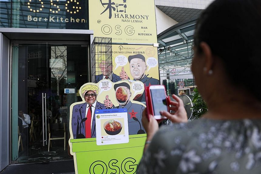 Summit frenzy is in full swing as people snap photos with a cut-out standee featuring US President Donald Trump and North Korean leader Kim Jong Un advertising a summit-themed dish at a restaurant in Singapore.