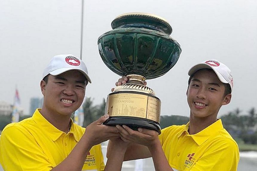 Singapore's junior golfers Andre Chong (far left) and Sean Lee lifting the trophy in Jakarta yesterday. Andre was second in both the boys' A Division and overall, while Sean was joint second in the boys' B Division.