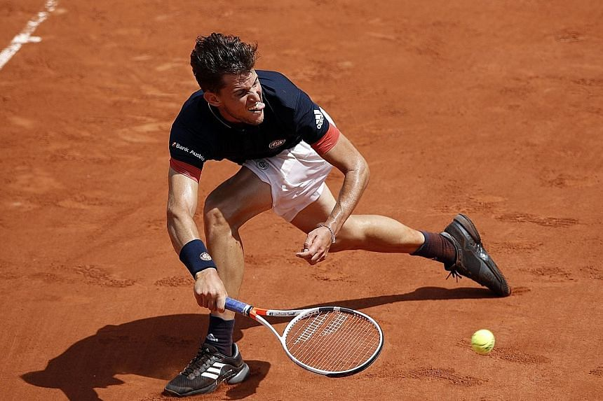 Austrian seventh seed Dominic Thiem scrambles for a forehand during his 7-5, 7-6 (12-10), 6-1 victory against unseeded Marco Cecchinato of Italy yesterday. Cecchinato eliminated three seeds, including Novak Djokovic, during his electrifying run to th