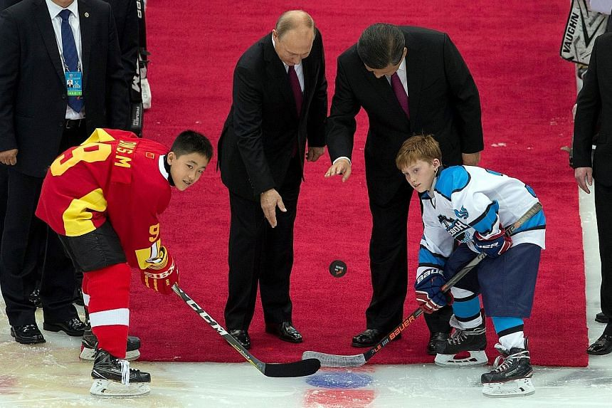 Left: Chinese President Xi Jinping presenting Russian President Vladimir Putin with the Friendship Medal in Beijing yesterday. Above: The two leaders dropping the puck to start a friendly match between the Chinese and Russian youth ice hockey teams i