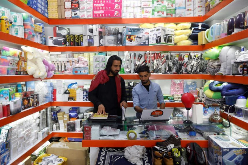 Shopkeepers work on their laptop at their online shop in Kabul on June 4, 2018.
