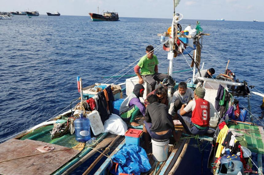 Filipino fishermen eat a meal aboard a fishing boat overlooking Chinese fishing vessels at the disputed Scarborough Shoal on April 6, 2017.