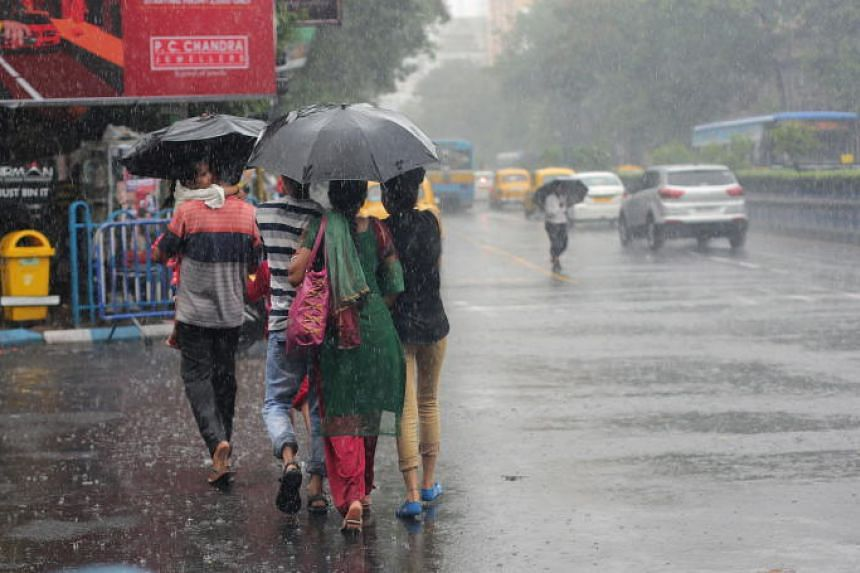 Commuters cross the main road during wind and heavy rain in Kolkata, Eastern India, on June 7, 2018.