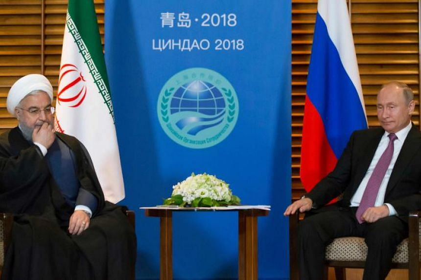 Russian President Vladimir Putin meets Iranian President Hassan Rouhani on the sidelines of the Shanghai Cooperation Organisation Summit in Qingdao on June 9, 2018.