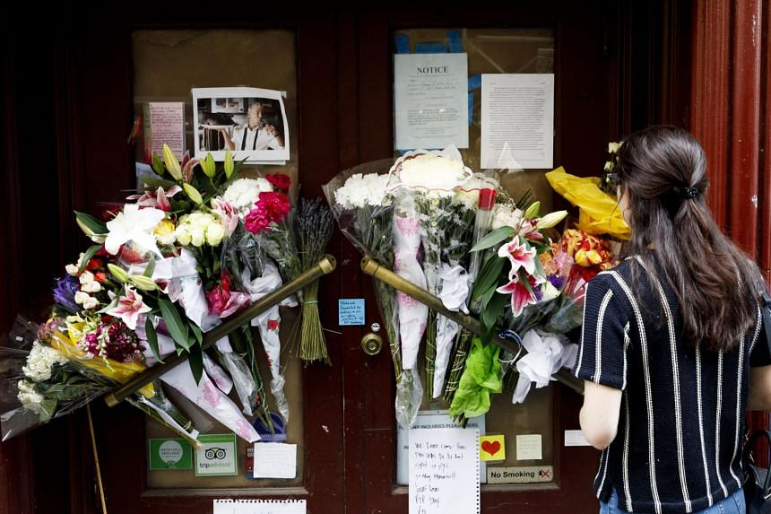 People look at notes and flowers left for the late CNN host and chef Anthony Bourdain in front of the now-closed restaurant, Les Halles, which he originally opened, in New York, on June 8, 2018.