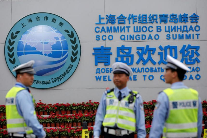 Security personnel stand guard in front of a sign of the Shanghai Cooperation Organisation in Qingdao, China, on June 8, 2018.