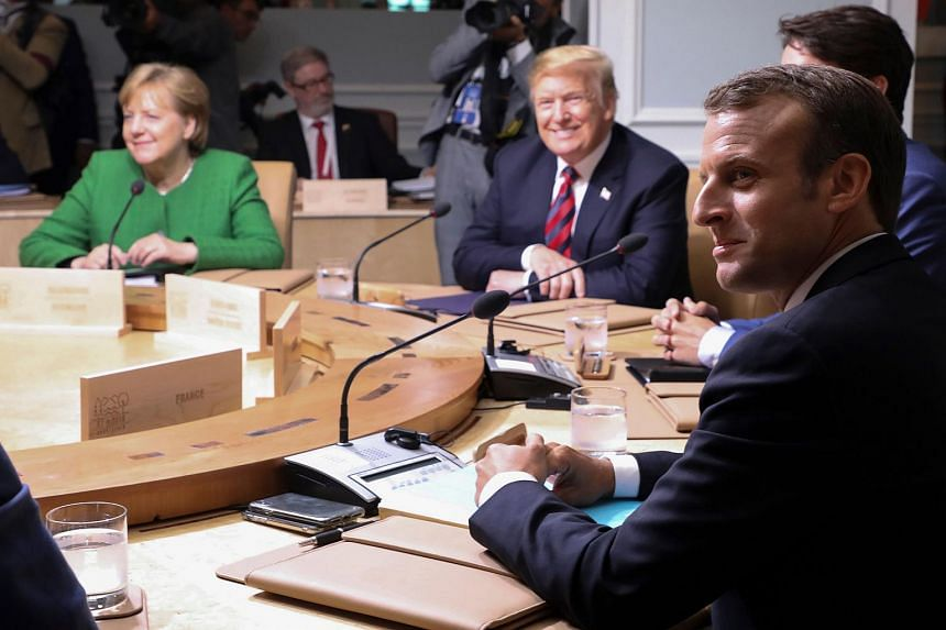 German Chancellor Angela Merkel (left), US President Donald Trump (second, left), and French President Emmanuel Macron participate in a working session of the G7 Summit, on June 8, 2018.
