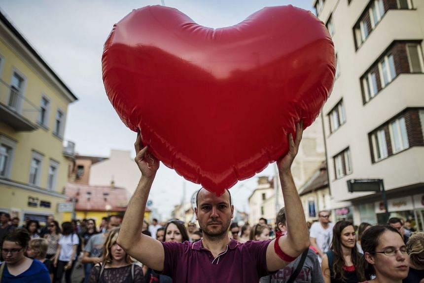 A man holds a heart-shaped balloon as thousands of Slovaks rally in Bratislava.