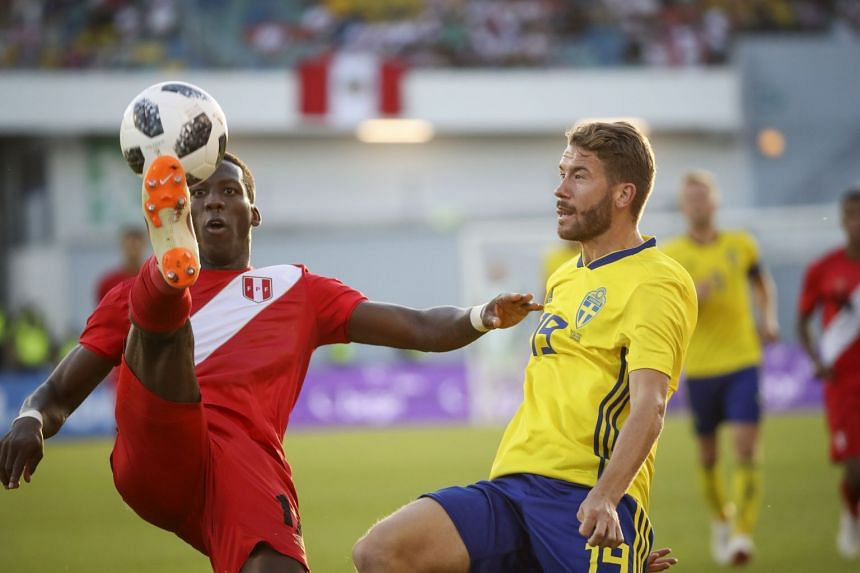 Peru's Luis Advincula (left) and Sweden's Marcus Rohdén fight for the ball.