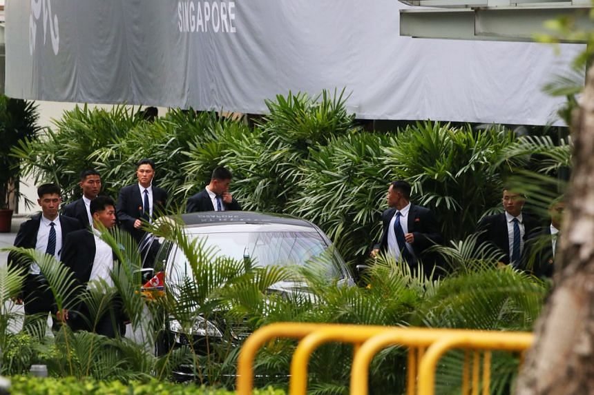 Members of the security detail jog alongside one of the cars in Kim Jong Un's motorcade to the St Regis, on June 10, 2018.