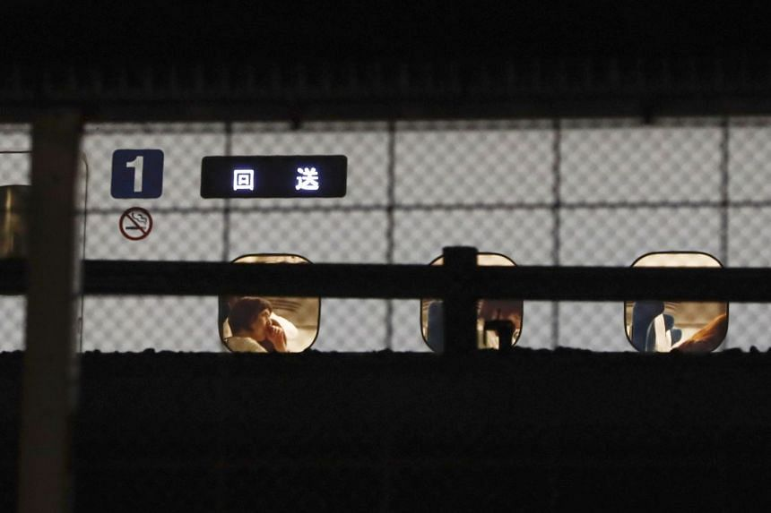 Passengers are seen inside a Japanese Shinkansen bullet train after it made an emergency stop on its way to Osaka.
