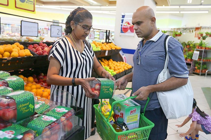 Madam Pusphavalli's husband, Mr Selvam Sundram, helping her to carry the load at the supermarket as she is not supposed to lift more than 2kg of items on her right side. She used to haul heavy bags of groceries home on her own.