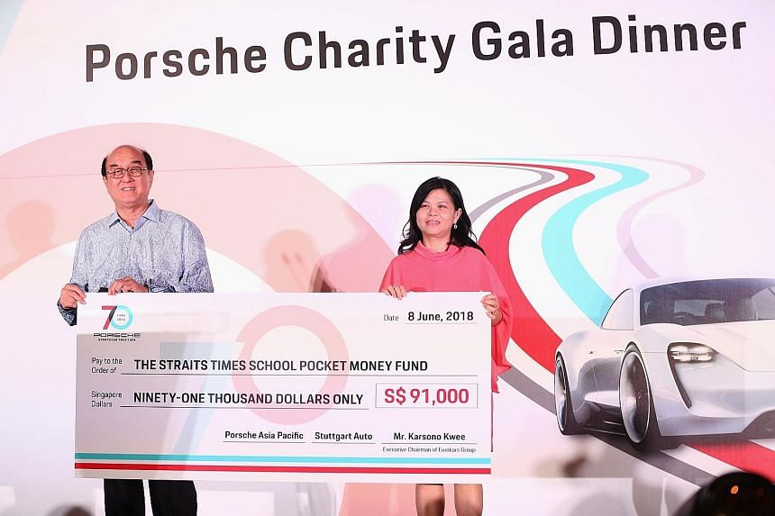 Eurokars Group executive chairman Karsono Kwee presenting a $91,000 cheque for The Straits Times School Pocket Money Fund to Ms Tan Bee Heong, the fund's general manager, at the Porsche charity gala dinner to mark the 70th anniversary of the German c