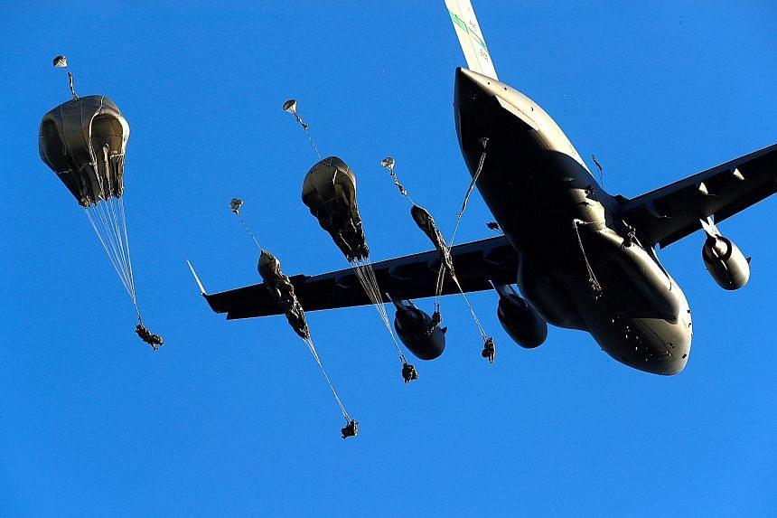 United States Army paratroopers dropping out of a C-17 aircraft during the Nato exercise Swift Response 2018 in Adazi, Latvia, yesterday. Swift Response is a series of exercises taking place in Eastern Europe that is designed to strengthen the abilit