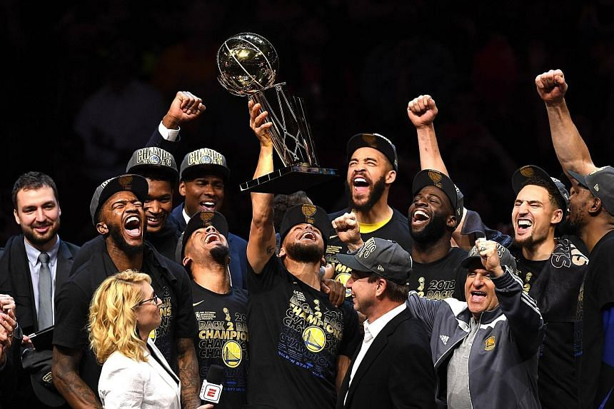 Stephen Curry lifting the Larry O'Brien trophy to his team-mates' cheers after the Golden State Warriors beat the Cleveland Cavaliers 108-85 in Game 4 to win the NBA Finals for the third time in four years.