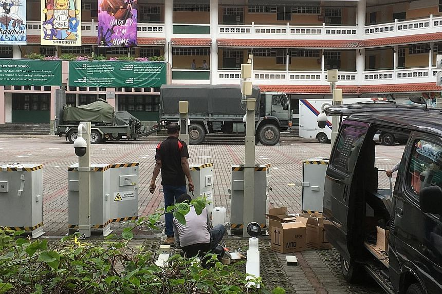 (Left) An officer diverting traffic in Tomlinson Road towards Cuscaden Road yesterday. (Above) A security scanner outside the entrance of The St Regis Singapore hotel. Workers setting up mobile cameras in the carpark of Raffles Girls' School in Ander