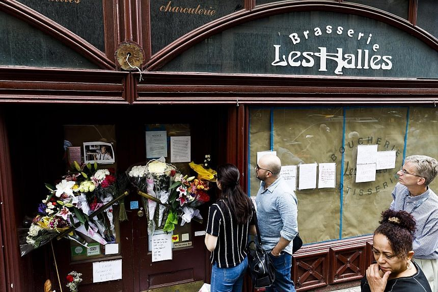 """Notes and flowers left for the late CNN host and chef Anthony Bourdain in front of the now-closed restaurant, Les Halle, in New York. """"Everyone in the food business in this generation owes him a lot,"""" says chef, restaurateur and cookbook author Edwar"""