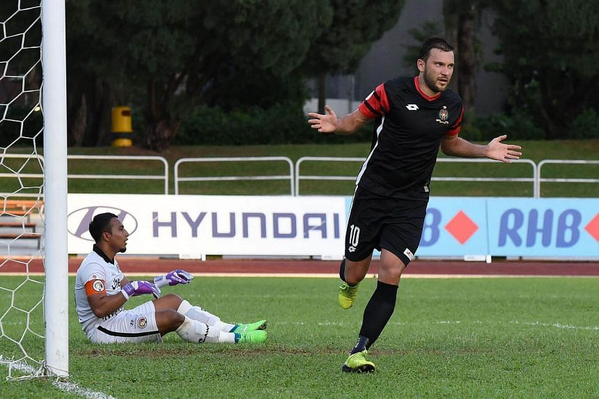 Brunei DPMM player, Volodymyr Pryiomov (right) celebrates after scoring a goal.