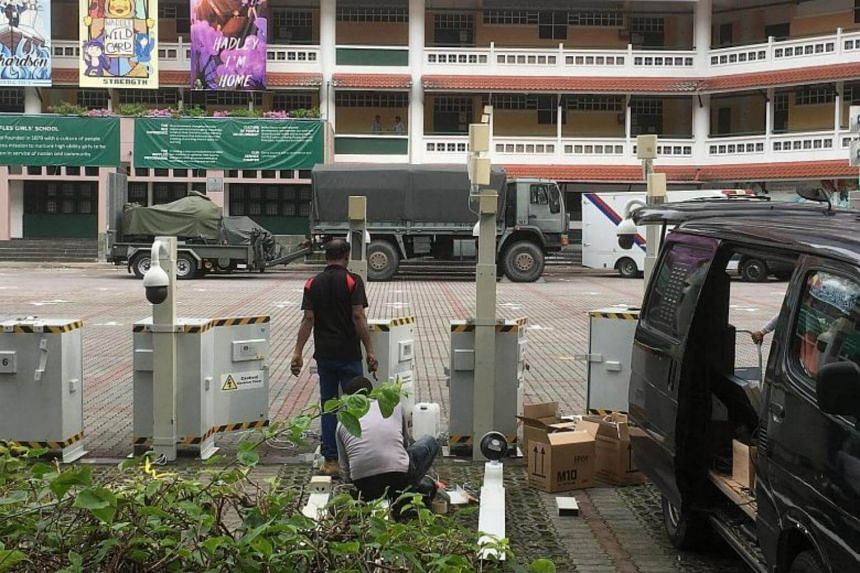 Workers setting up mobile cameras in the carpark of Raffles Girls' School in Anderson Road yesterday, as preparations for the Trump-Kim summit take place in the area, including Orchard Road and Tanglin Road.