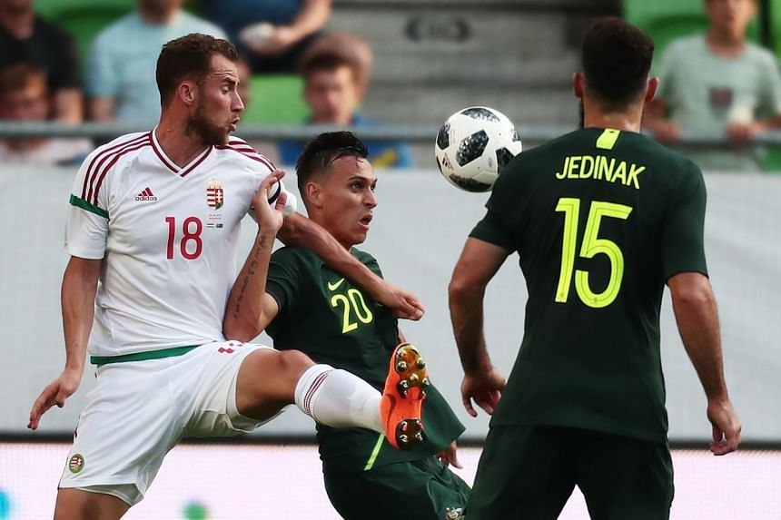 Hungary's Marton Eppel (left) vies for the ball with Australia's Trent Sainsbury (centre).