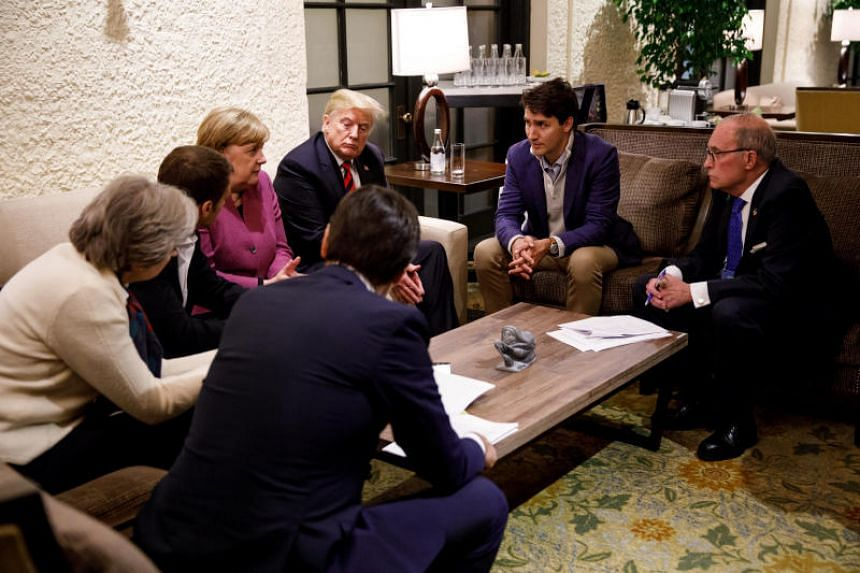Canada's Prime Minister Justin Trudeau and G7 leaders France's President Emmanuel Macron, Germany's Chancellor Angela Merkel, Britain's Prime Minister Theresa May and US President Donald Trump hold a meeting with staff on the first day of the G7 meet