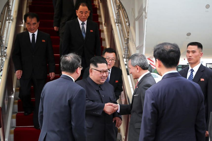Singapore's Foreign Minister Vivian Balakrishnan welcomes North Korean leader Kim Jong Un on his arrival in Singapore, on June 10, 2018.