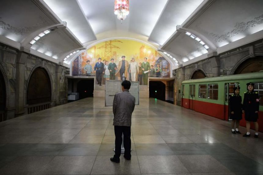 A commuter reads a newspaper displayed on the platform of a subway station in Pyongyang.
