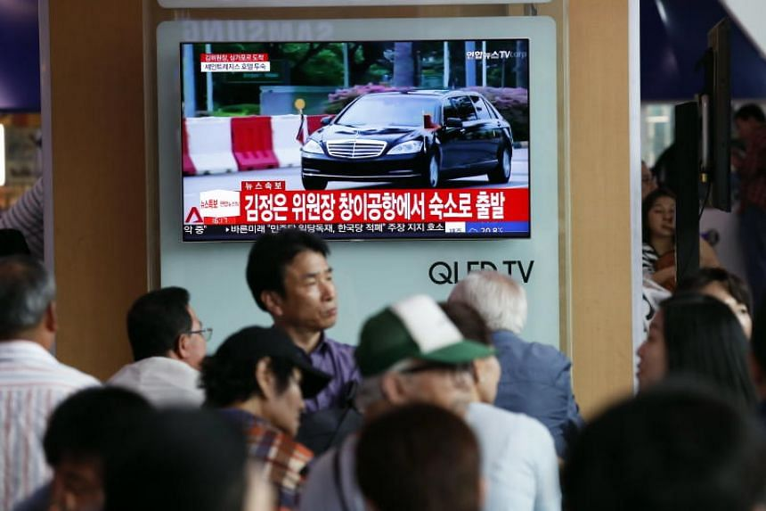 South Koreans watching a news programme on the arrival of North Korean leader Kim Jong Un in Singapore, in Seoul Station on June 10, 2018.