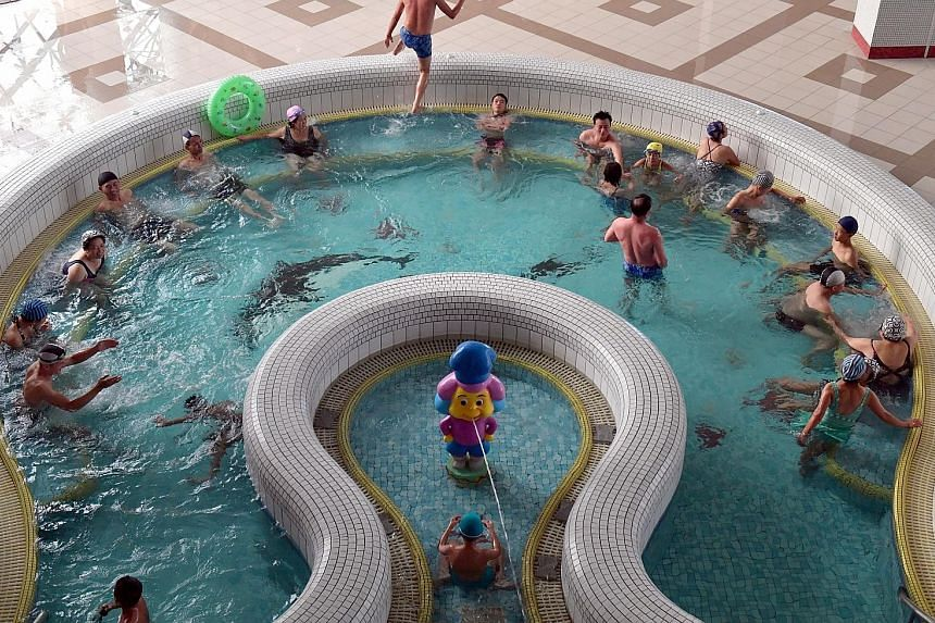 Farmers and workers head back to their ancestral homes on a weekend outside Jang Chon Cooperative farm, which is a 30-minute drive from Pyongyang. Above: The state-run Munsu Water Park covers 15ha and has nine pools, nine saunas and water rides - all