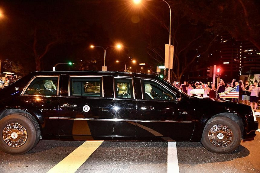 Armed police officers on patrol yesterday outside the Shangri-La Hotel, where Mr Trump is staying. US President Donald Trump waving at bystanders from inside his presidential limousine along Anderson Road last night. Hundreds of people lined the stre