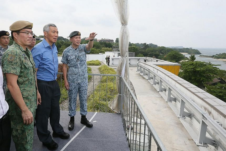 Prime Minister Lee Hsien Loong speaking to officers on duty during his visit to the Home Team command post in Novena yesterday. PM Lee with Chief of Defence Force Melvyn Ong (left) and Director of Joint Operations Tan Chee Wee on the rooftop of Sento