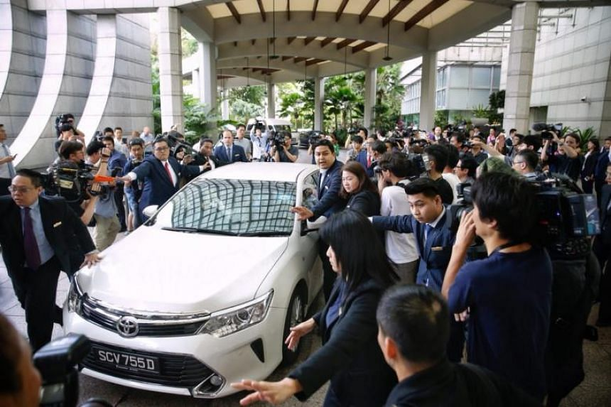 Media scrum around the vehicle of US envoy Sung Kim as he departs The Ritz-Carlton Millenia Singapore after talks with North Korean Vice-Foreign Minister Choe Son Hui on June 11, 2018.