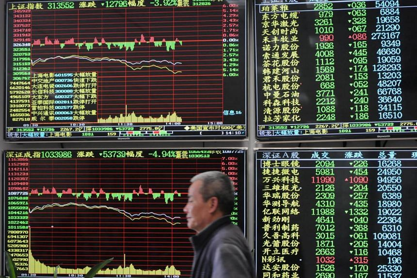 File photo showing a man against an electronic board showing stock information at a brokerage house in Jiujiang, Jiangxi province, China, on March 23, 2018.