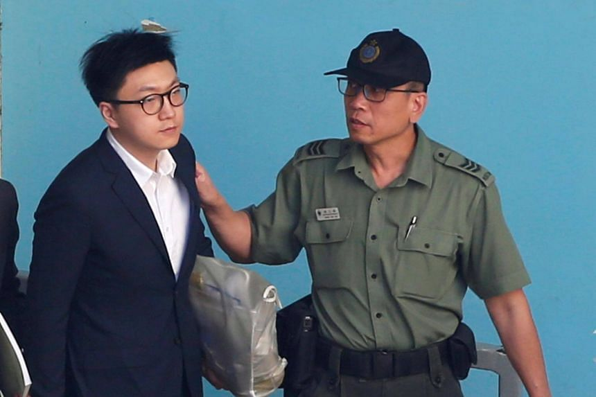 Pro-independence activist Edward Leung is held by a correctional services department officer inside a detention centre before leaving for the High Court for a sentencing hearing, on June 11, 2018.