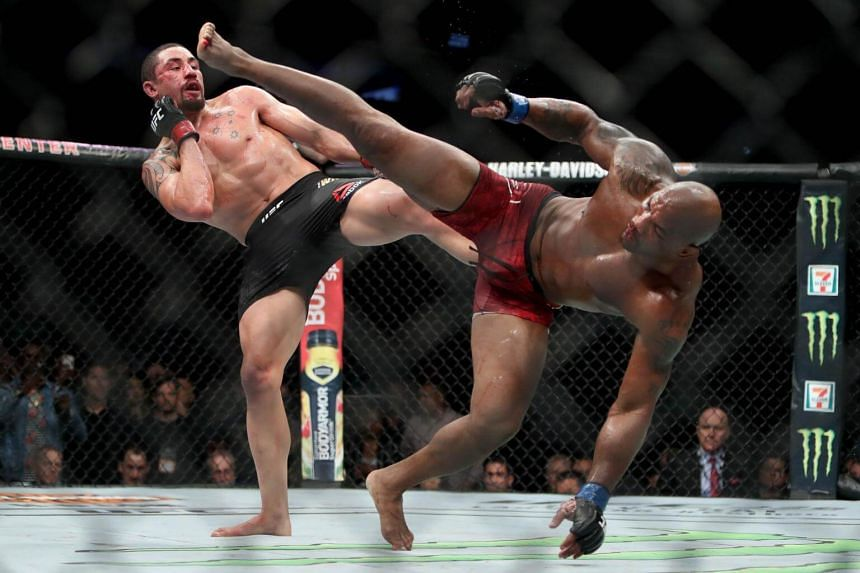 Robert Whittaker of New Zealand (left) and Yoel Romero of Cuba each attempt a kick in the fifth round in their middleweight title fight, on June 9, 2018 in Chicago, Illinois.
