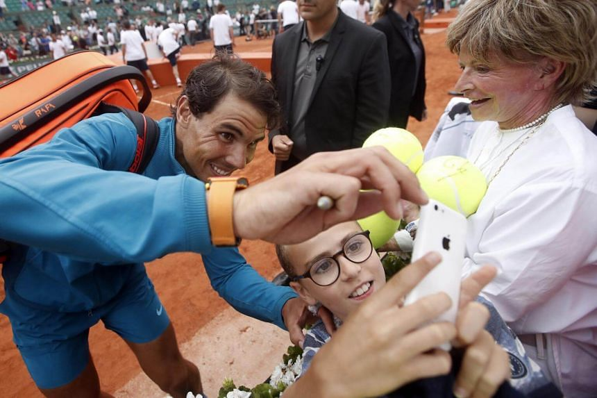 Rafael Nadal of Spain taking a selfie with a fan after the men's final match at the French Open on June 10, 2018.