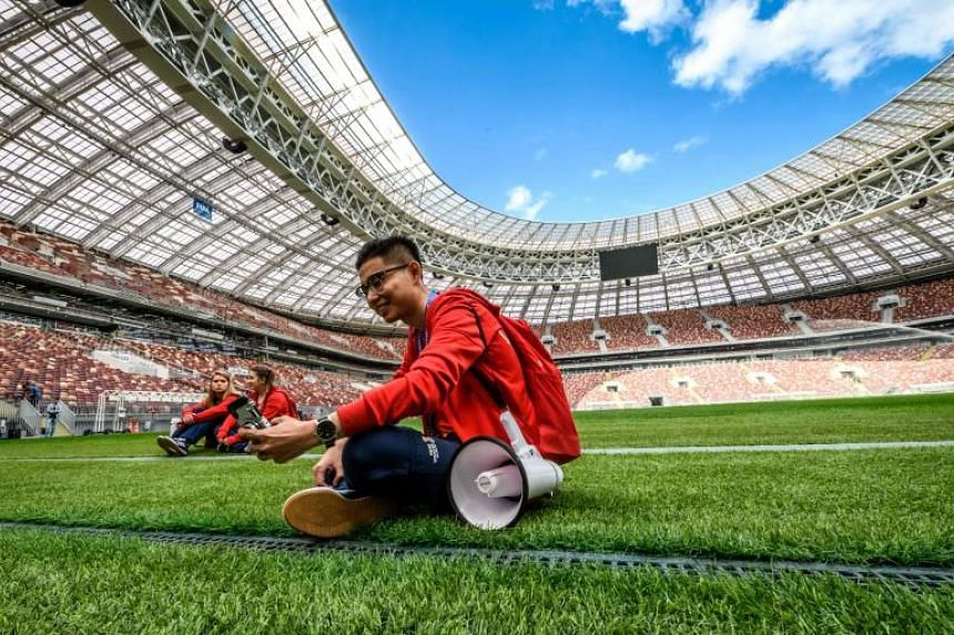 Volunteers sit on the pitch of the Luzhniki Stadium in Moscow on May 23, 2018.