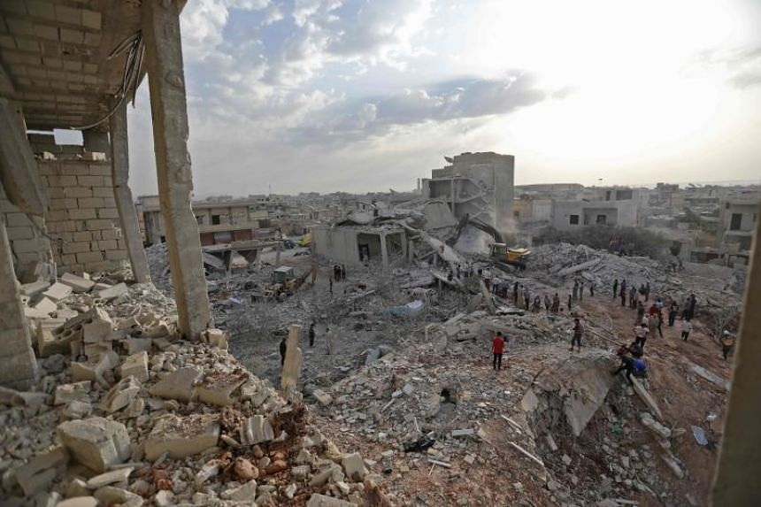 Syrians gather amidst destruction in Zardana, in the mostly rebel-held northern Syrian Idlib province, in the aftermath of following air strikes in the area late on June 8, 2018.