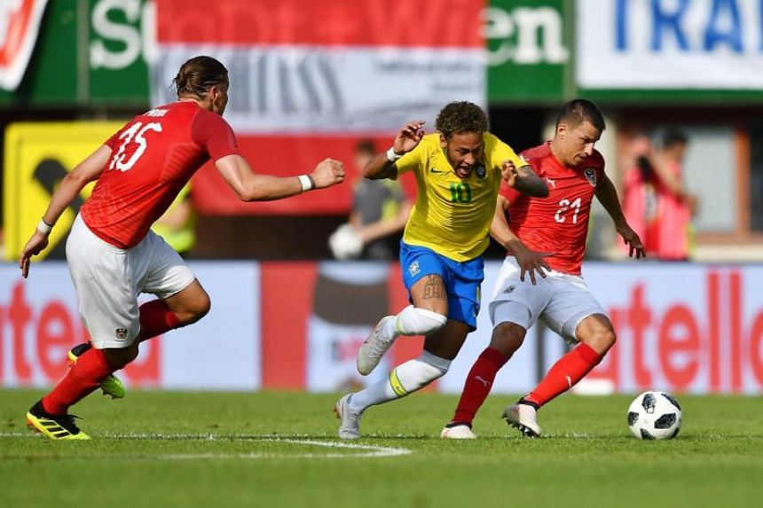 Brazil's forward Neymar (centre) and Austria's defender Stefan Lainer vie for the ball during the international friendly footbal match Austria vs Brazil in Vienna, on June 10, 2018.