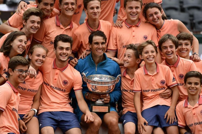 Rafael Nadal poses with his trophy and ballboys after winning against Dominic Thiem during their men's final match during the French Open in Paris on June 10, 2018.