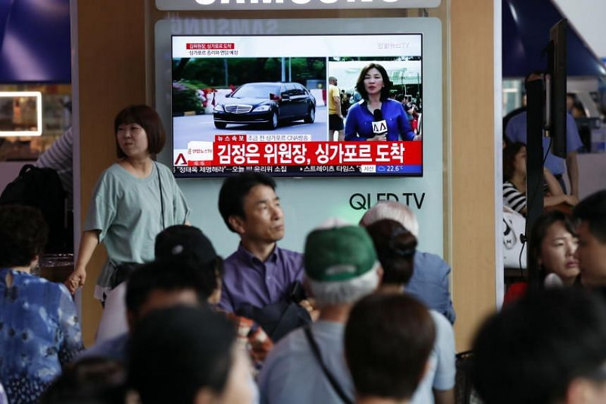 South Koreans watching a TV news broadcast on North Korean leader Kim Jong Un's arrival, at Seoul Station, on June 10, 2018.