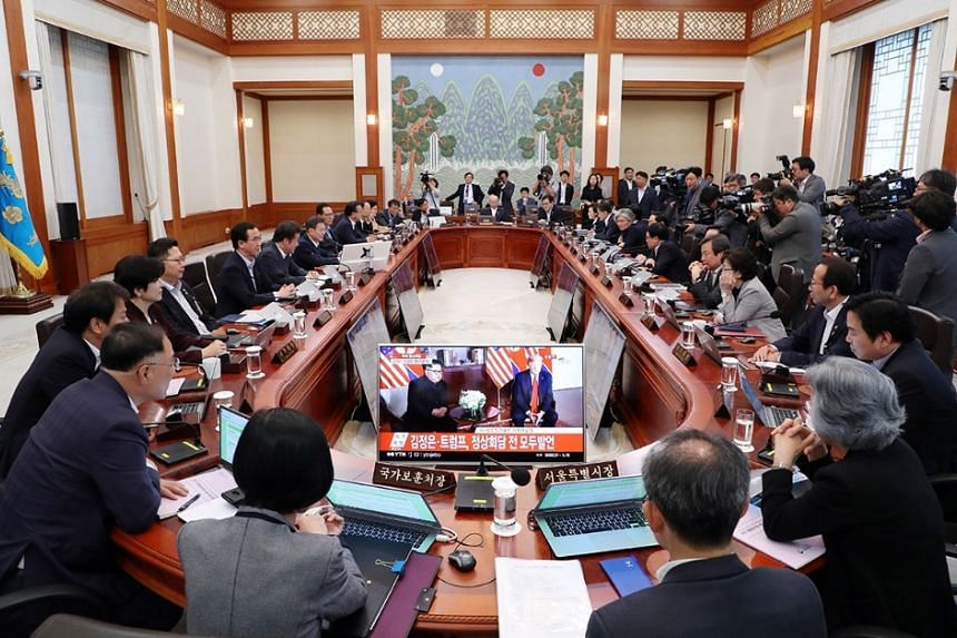 South Korean President Moon Jae In (middle) watches a live broadcast of the Trump-Kim during a Cabinet meeting, on June 12, 2018.