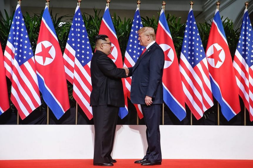 North Korean leader Kim Jong Un and US President Donald Trump shake hands ahead of their historic summit at the Capella Singapore, on June 12, 2018.
