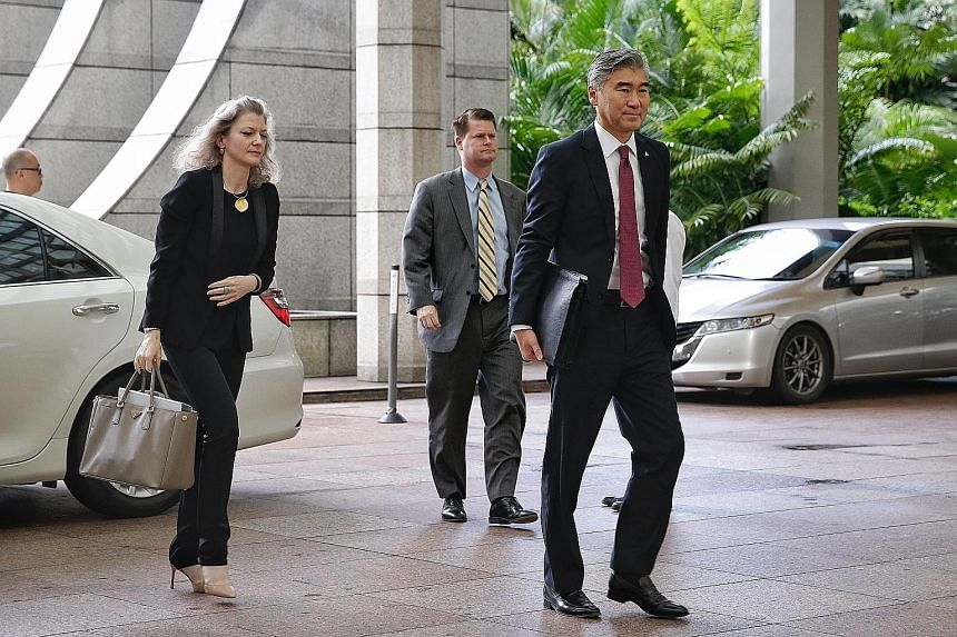 American officials (left), led by US Ambassador to the Philippines Sung Kim, and North Korean officials (right), led by the country's Vice-Foreign Minister Choe Son Hui, arriving at The Ritz-Carlton, Millenia Singapore yesterday morning for working-l