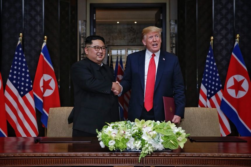 """US President Donald Trump and North Korean leader Kim Jong Un shake hands after signing a """"comprehensive"""" document at the end of their summit, on June 12, 2018."""