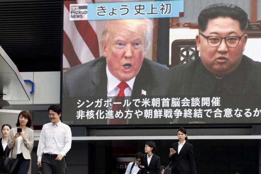 Pedestrians walk past a large screen displaying US President Donald Trump and North Korean leader Kim Jong Un, in Tokyo, Japan, on June 12, 2018.