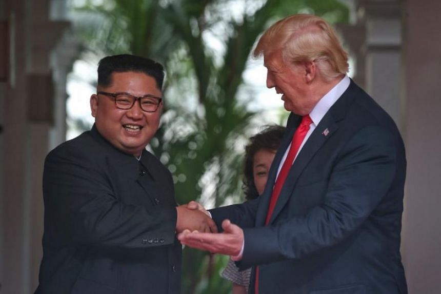 US President Donald Trump and North Korean leader Kim Jong Un having a short exchange while making their way for the one-on-one meeting at Capella Singapore on June 12, 2018.